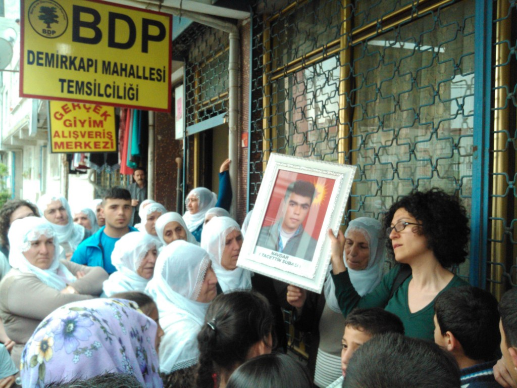 In front of the BDP office (Kurdish political party) a mother shows a picture of her son, who got killed in the conflict.
