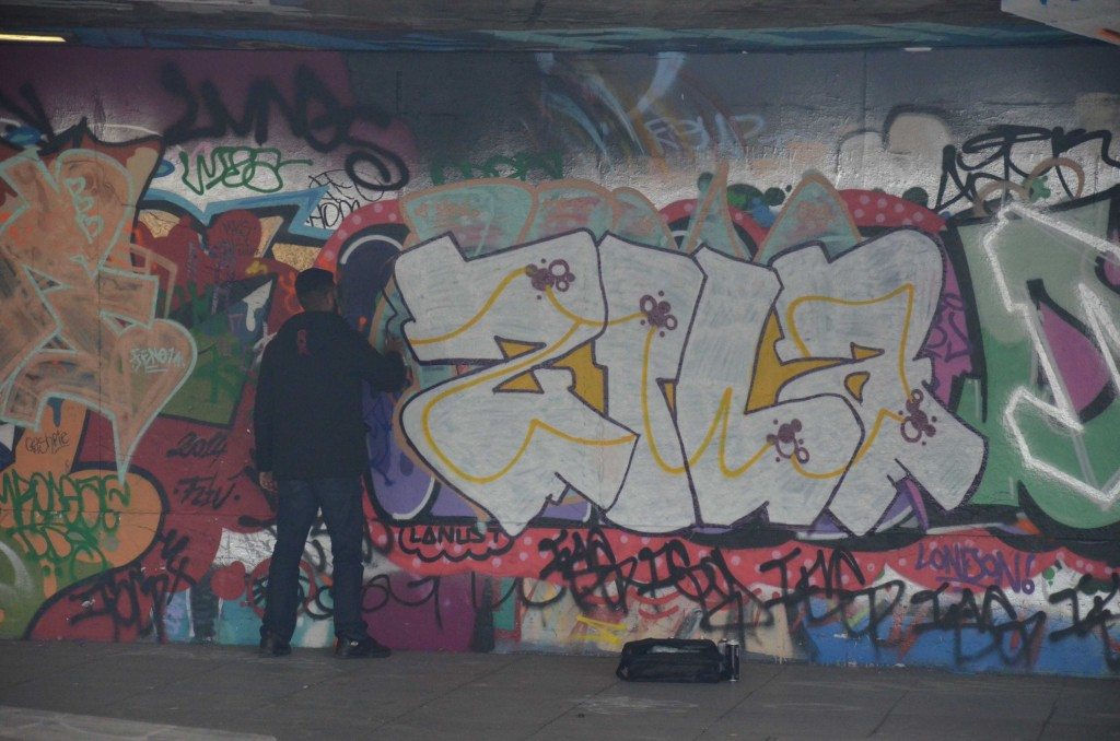 A graffiti artist adds his mark to the street art murals at the Undercroft. (Source: Kim von Schönfeld)